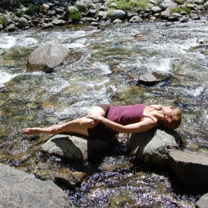 yoga supine twist on rocks in river