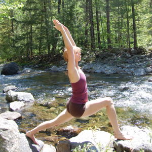 Woman Debbie in Warrior I on rocks next to a river practicing private yoga