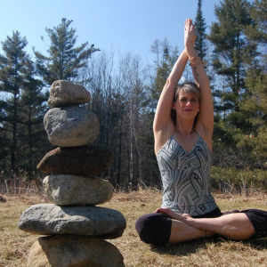 Debbie woman sitting in lotus pose with arms overhead palms together outdoors with trees in background and stack of stones in foreground virtual private yoga